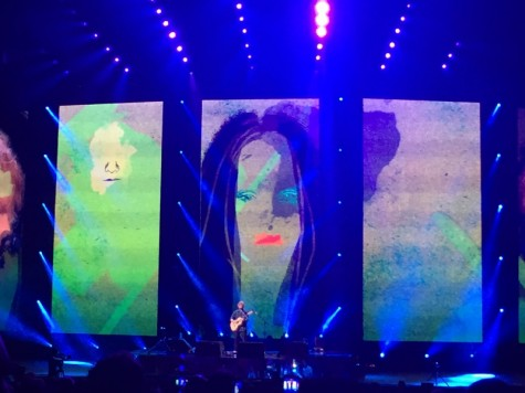 Sheeran plays a song with interesting graphics in the background.