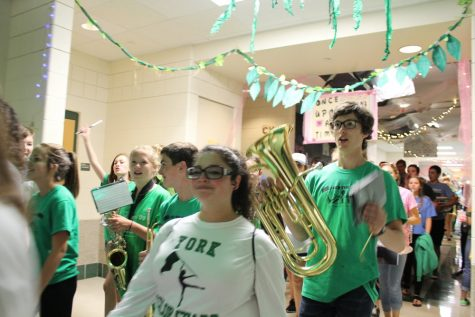Sam Griffin, euphonium player and junior, cheers on the band while following flags member Amethyst Nieves, senior.