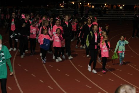 Cheerleaders lead the kids they worked with at their cheer clinic to the field.