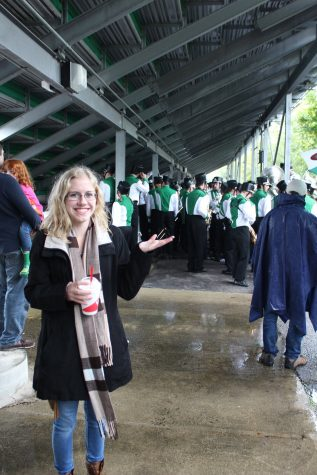 Tatum Langley takes a group picture with the marching band, keeping themselves dry until a break in the rain.