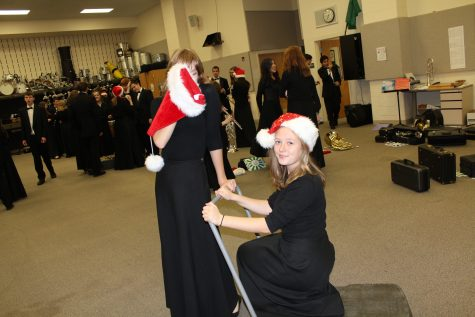 Sophomore Siena Olson hides behind a Santa hat while pulling saxophonist Grace __ on a makeshift sleigh.