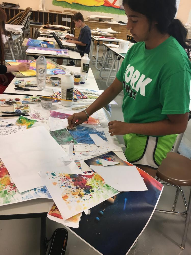 Sonali Kumar works on a collage painting.