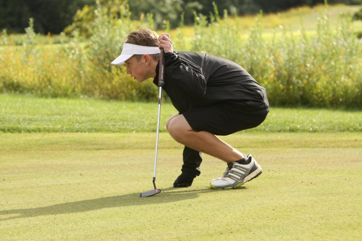 Sophomore Connor Polomsky debates how to line up his putt.
