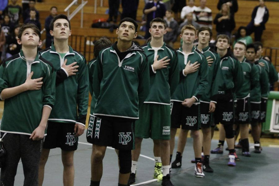 Varsity+Wrestling+stands+during+the+national+anthem+as+they+prepare+for+the+meet+to+start.+