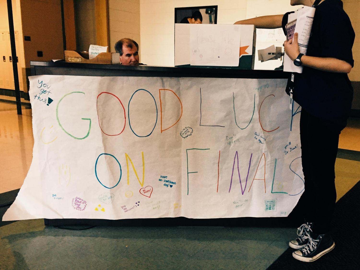 """A student grabs candy after reading the """"Good Luck on Exams"""" in the academic entrance"""