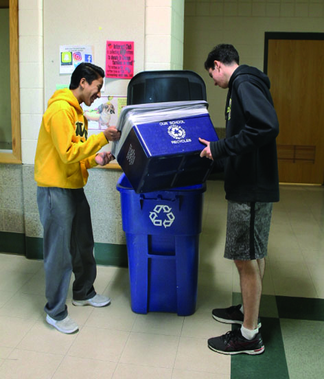 Sophomores Roshan Hoffman (left) and Mike Campbelll (right) further prove how the new program is a collaborative effort by emptying recycling bins into the ones in the hallway.
