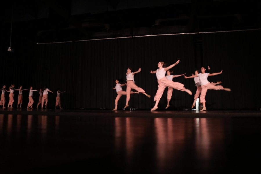 Students sauté across the stage during their performance of
