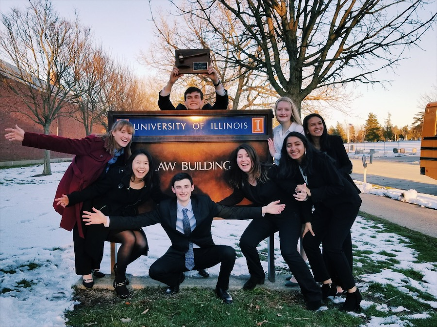 The varsity team basks in their victory as they pose around the University of Illinois College of Law sign.