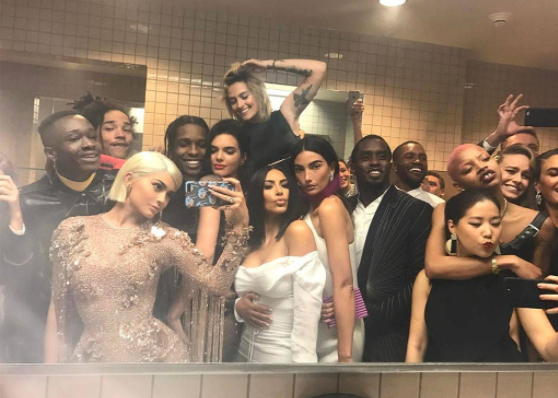 Attendees of the 2017 MET Gala crowd around a bathroom mirror as they pose for a selfie taken by Kylie Jenner.