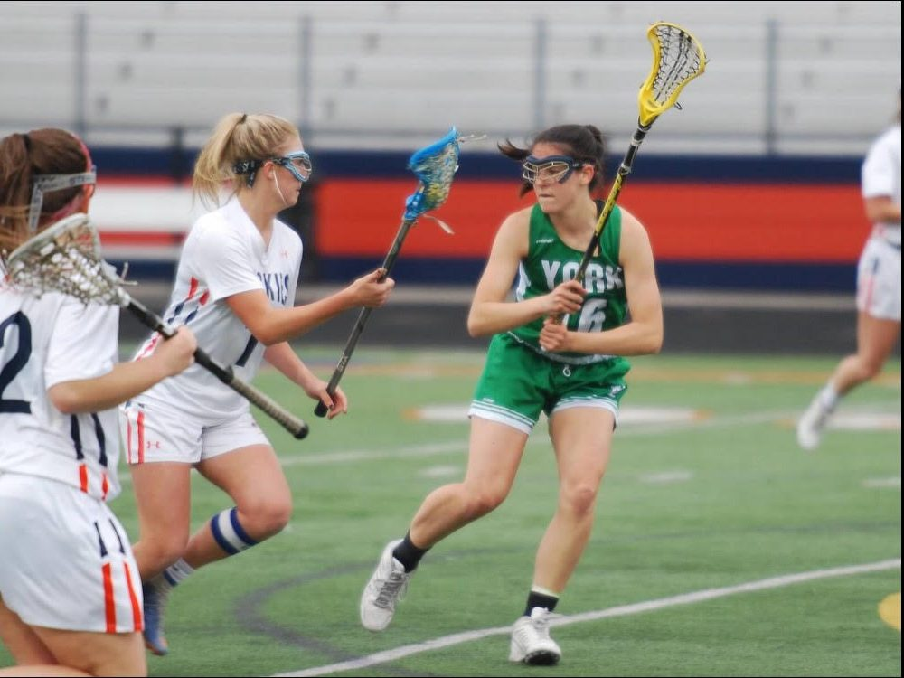 In a lacrosse game against Naperville North, Mollie Grasse is determined to get the ball from the other team.