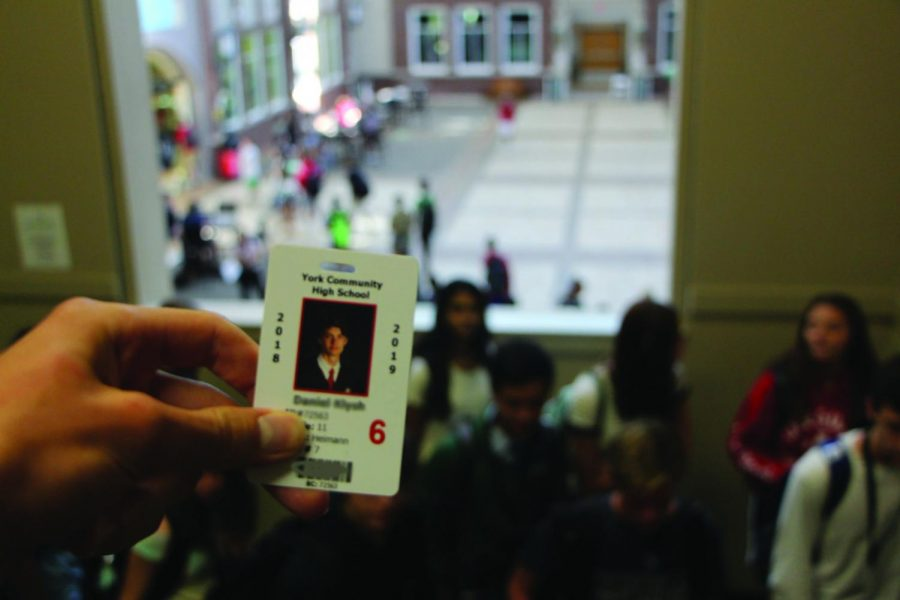A student presents his ID before entering the cafeteria.