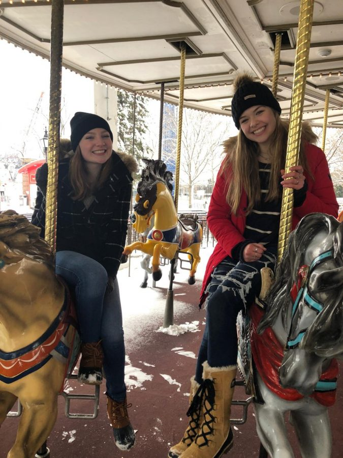 Junior Holly Kauck and Gracie Weinstein riding the carousal on a cold day in Holiday in the Park.