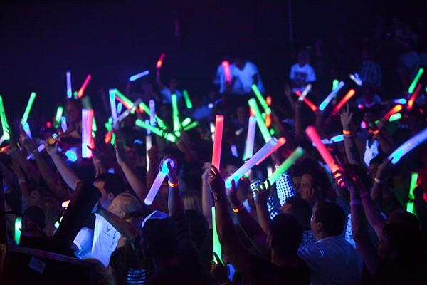 People  enjoy the festivities of a black light dance.