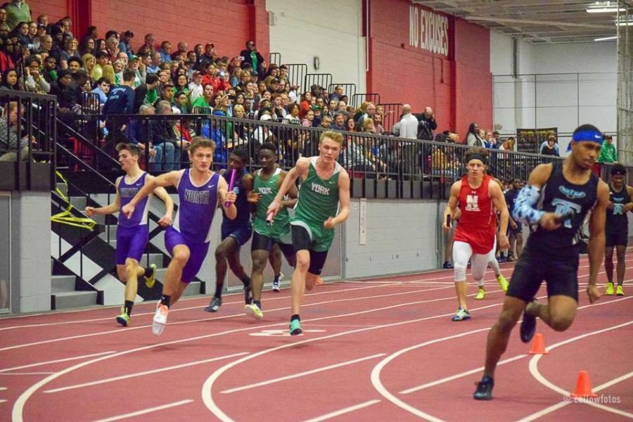 Sophomore Chris Radcliff rounds the turn after receiving the baton. Photo courtesy of callow photos