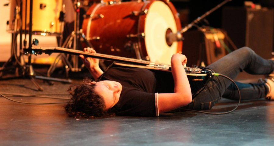 Senior Maya Toffler chills out on the ground during her performance with senior Ben Pavlik. Photo by Maddy McGreal.