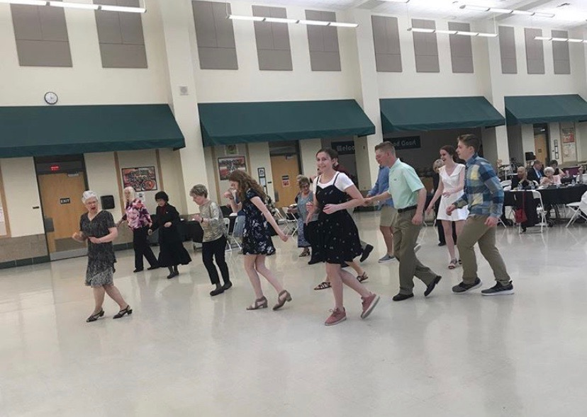 York students join the senior citizens on the dance floor for the Boot Scootin Boogie.