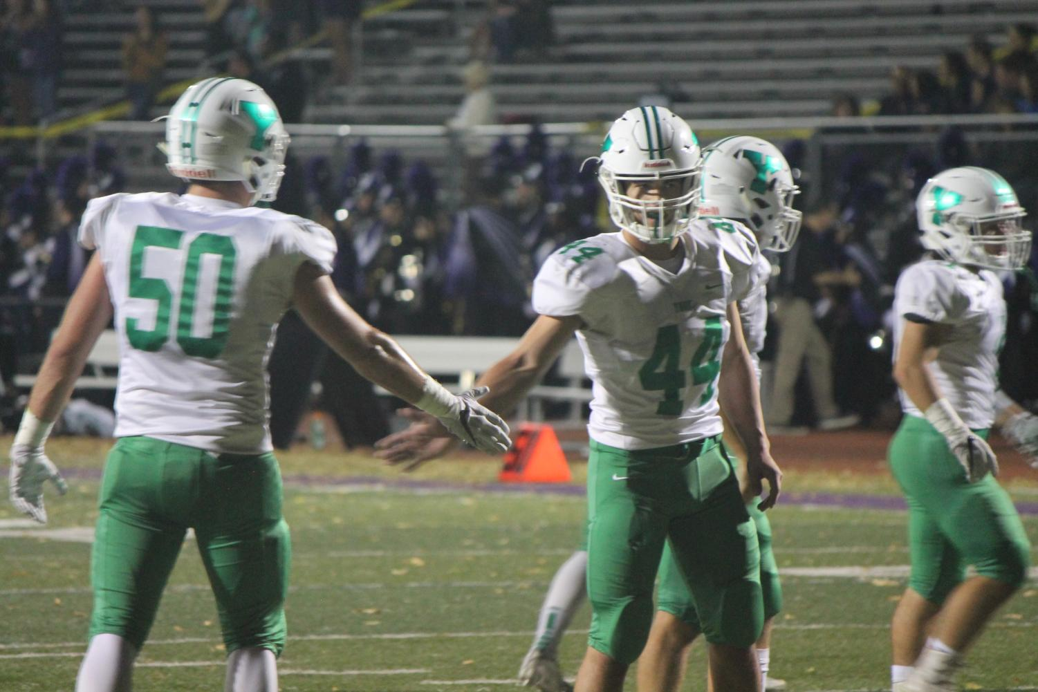 Seniors Liam Enright (50) and Chris Eckard (44) dap each other up after making a big play.
