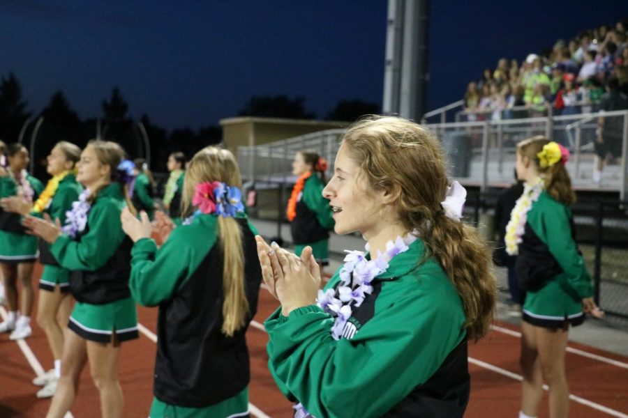 Freshman Holly Jo Gollias claps alongside the rest of her team as they support York.