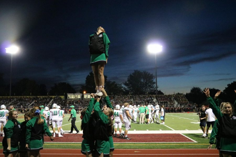 The cheer team performs stunts for the stands to hype them up for the game.