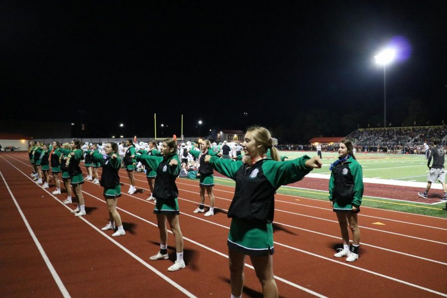 The cheer team faces the stands to pump everyone up for the first Friday night football game of the season.