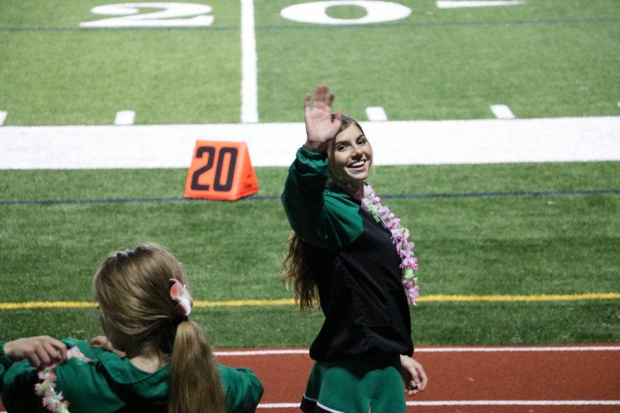 Sophomore Bree Spalone waves to the stands full of students decked out in Hawaiian clothing.