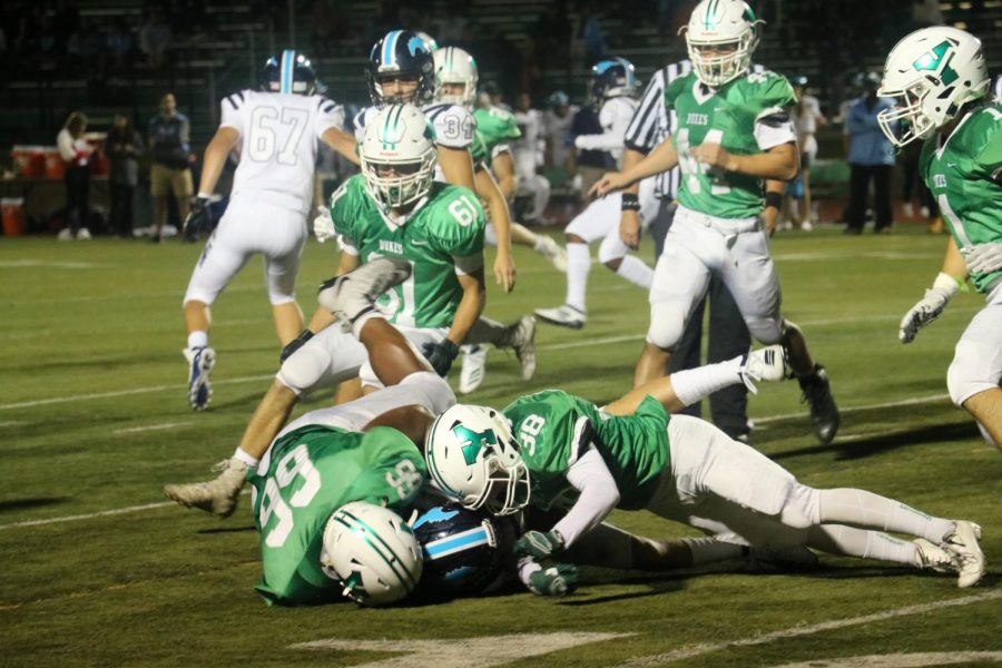 On defense, senior Josh Mathiasen and junior Hayden Raniere tackle a member of Downers Grove South.