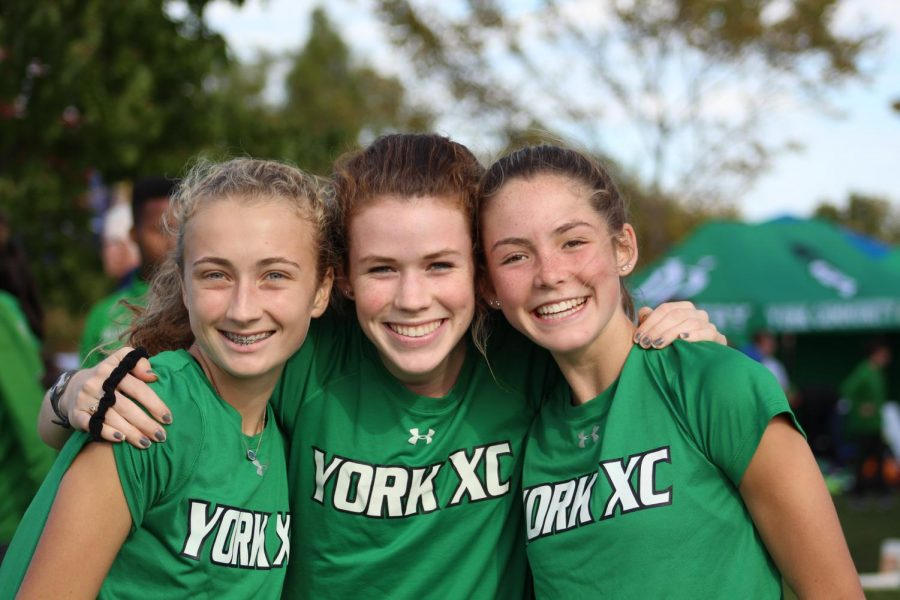 Sophomore Kathleen Buhrfiend, senior Lydia Hickey, and sophomore Katelyn Winton pose for the camera before running in the varsity race. Oct. 19, 2019.