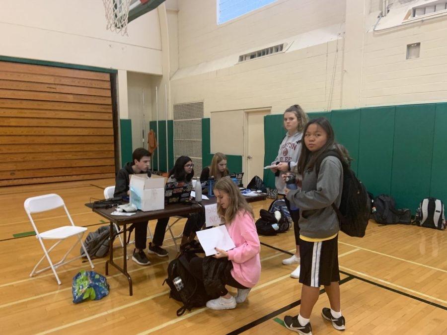 Student council members help the students check in by making sure they have the correct forms and are excused from their class.