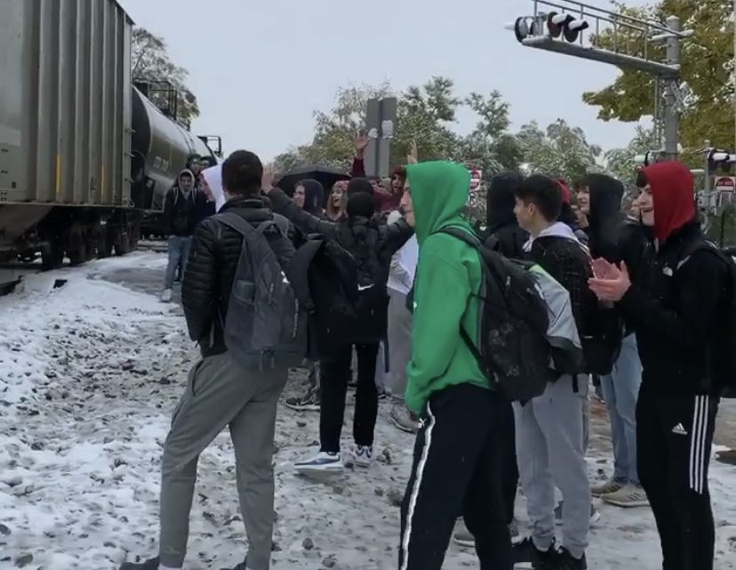 Students celebrate as the train finally clears the track after 40 minutes of waiting.