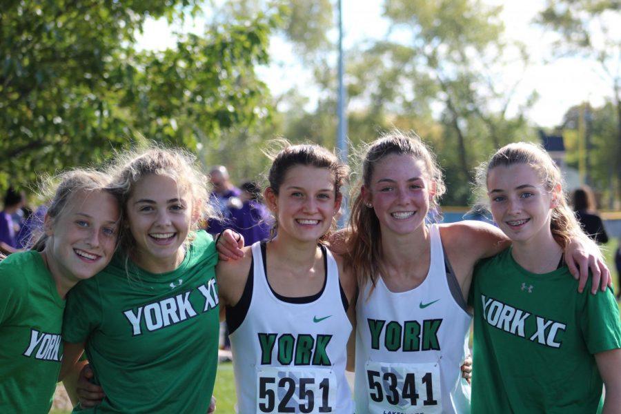 Freshman Kate Pratt, sophomore Bella Swanson, freshman Brooke Berger, sophomore Katelyn Winton and freshman Maureen Buhrfiend share hugs after completing their races. Oct. 19, 2019.