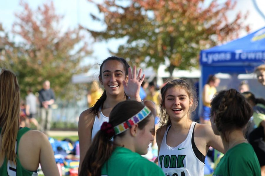 Seniors Mary Kritikos and Mary Clare Hughes get excited as they complete their pre-race drills. Oct. 19, 2019.