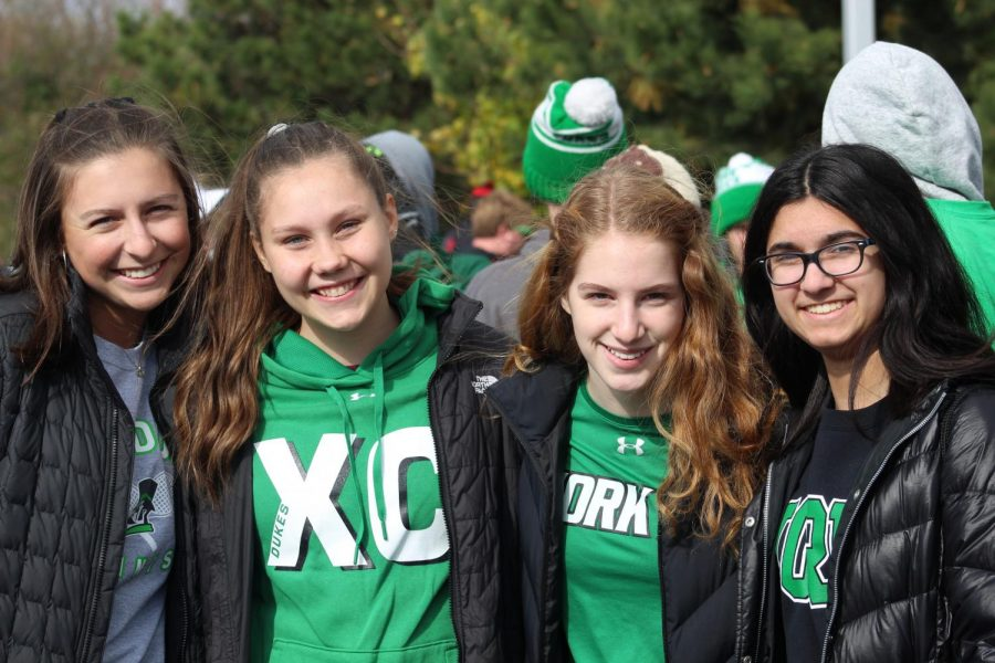Sophomores Maria Chornij, Maeve Maietta, Mira Shortt and junior Meaghan Scholtis enjoy the tailgate with other York students.