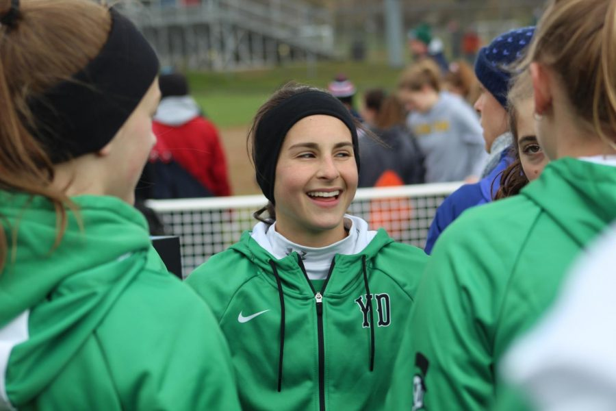 Sophomore Katelyn Leonard smiles while chatting with teammates before their drills.
