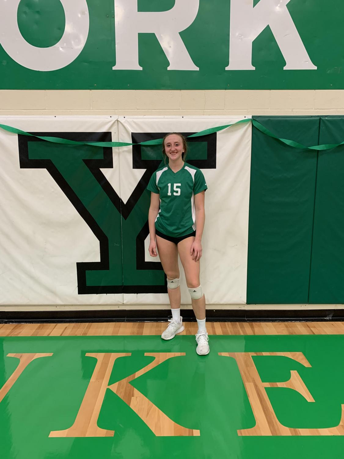 Junior, Gigi Barr, poses in front of Y logo after beating Lyons Township.