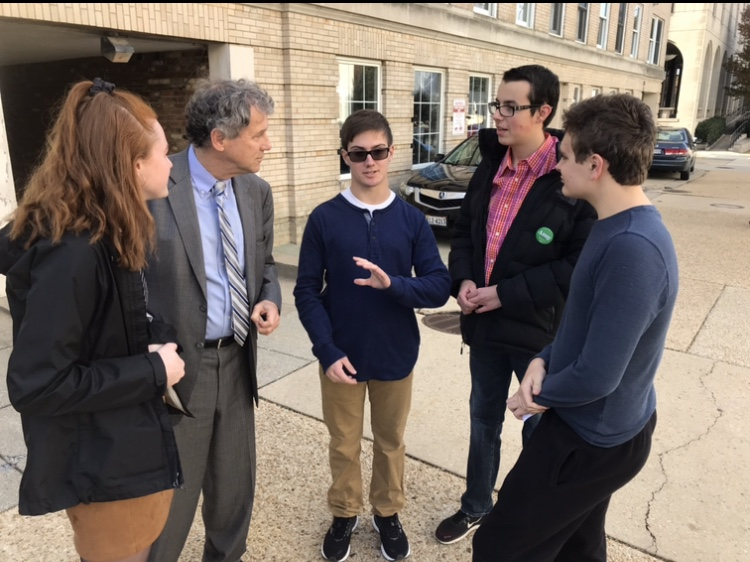 Seniors Julia DeMotte,  Ethan Thomas, Graham Reid, and Nick Mastro discuss college plans with Sen. Sherrod Brown (D-OH) outside the Democratic Senate Campaign office on Capitol Hill.