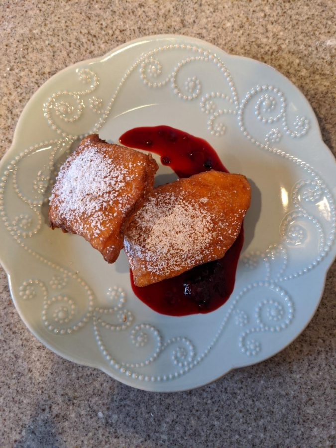 Once the sauce and beignets are done,  plate the beignets with the sauce. Make a dash of sauce across a plate and set the beignets on top.