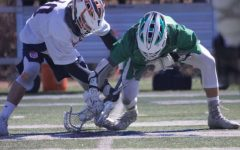 Senior Harrison Proud takes a face-off in a game last spring, the 2019 season, against the Glenbard West Hilltoppers.