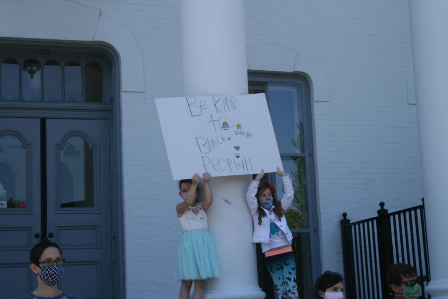 During the Elmhurst March for Equality, two girls stand on the steps of Wilder Mansion with a sign they created: