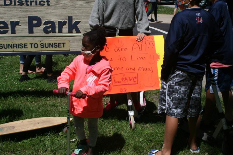 A young Elmhurst resident prepares her scooter in Wilder Park to travel the route designated for the Elmhurst March for Equality. June 13, 2020.