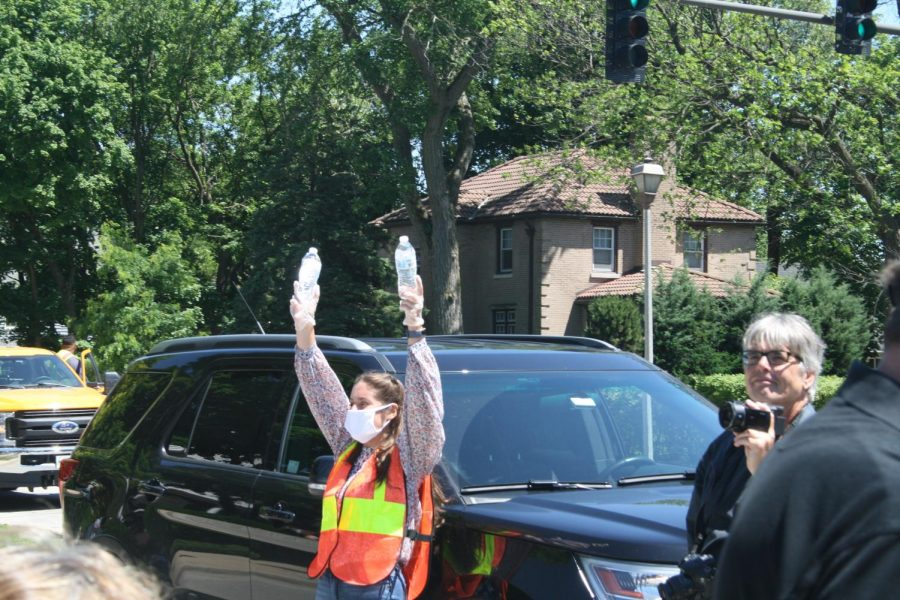 Graduate Carina Kanzler ('18), one of the primary organizers of the vigil in Wilder park, hands out waters to protesters during the Elmhurst March for Equality. June 13, 2020.