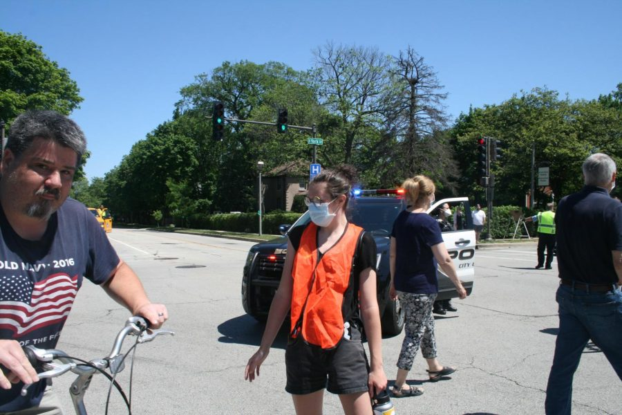 Graduate Eileen King ('18) directs traffic as a marshal volunteer for the Elmhurst March for Equality.
