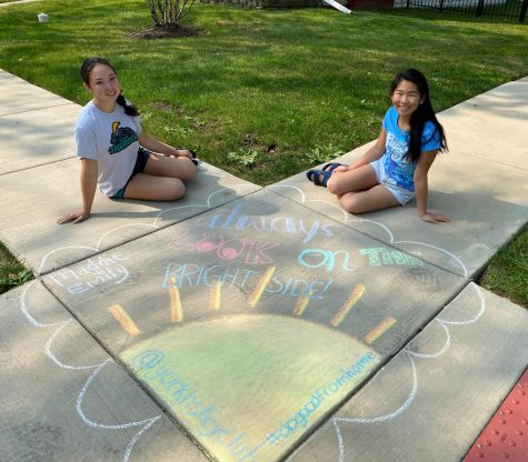 """Juniors Emily Fujiwara (left) and Madeleine Fine (right) show off their sunshine-filled chalk drawing. """"Right now with COVID, it can be extremely hard to feel like you have a voice in the community,"""
