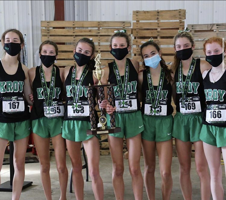 The Girls' Cross Country team pose with their championship trophy during the last state meet of the year. The team ended their season with a car parade.
