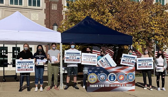 Members of Student Council stand in front of York with signs thanking Veterans for protecting our country. While a traditional Veterans Day assembly could not occur during the 2020-21 school year, Student Council still worked to honor the veterans in the community.