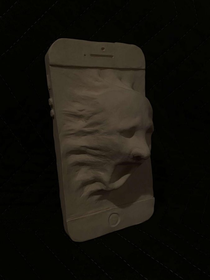 Photo of Matthew Milani's artwork for AP Art. Milani created a clay sculpture of a screaming face coming out of a phone in theme with his chosen sustained investigation, which depicts the relationship between people and technology.