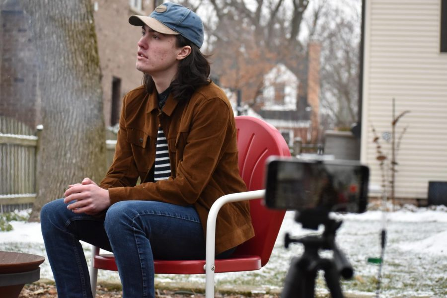 """Greg Perotti, played by student director and senior Charlie Kungl, interviews and listens intently to his scene partners. """"It's very interesting for me to play the person behind the camera,"""" Kungl said. """"It gives you a new perspective to the performance because while you're still acting and playing a character, what you do has no relevance to the story. You have to craft your character just right so they are complementary to the interviewee."""""""