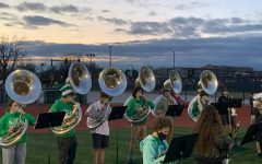 """A group of students in the Marching Band playing sousaphone line up to perform at a home football game.  """"Leading up to the first game, nothing really felt real-especially because of COVID-19 it's been hard to really look forward to something and expect it to happen,"""" senior Rose Menichini said. """"When we came back, it all finally set in and it was so much fun to walk out on the field again and hear the pep band songs."""""""