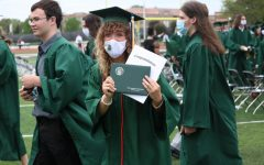 Graduate Jenna Hughes holds her diploma as she exits the ceremony to celebrate with family and friends.
