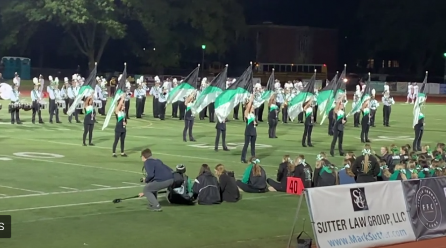 """Color Guard performing at a football game a year before the COVID-19 pandemic. """"My favorite part about color guard is being able to perform with such a fun and large group,"""" junior Kristina Vezmar said. """"We all support each other and have a lot of fun being loud and energetic during football games and pep rallies."""""""