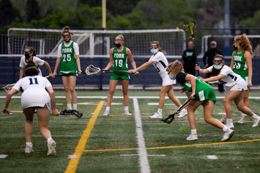 York students begin May with a variety of in-person and virtual events. Senior Jenna Hughes prepared for a free position shot in the game against New Trier on Monday. The Varsity Girls Lacrosse Team played an amazing game against the 2018 state champions in a game that ended with the final score being nine goals for York and 10 goals for New Trier.
